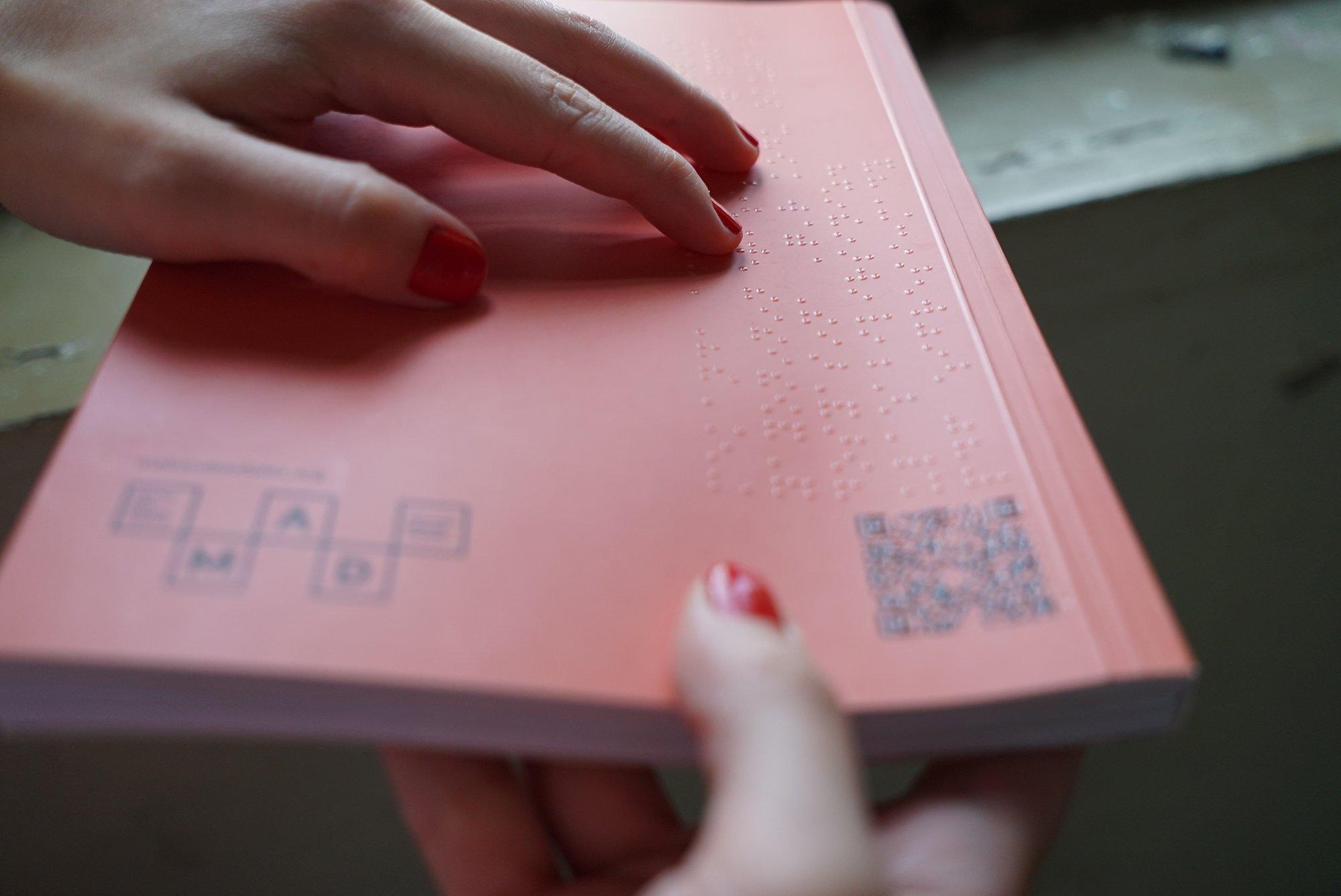 Dergiyi tutan bir çift el arka kapakta bulunan braille alfabesini okumaya çalışıyor.