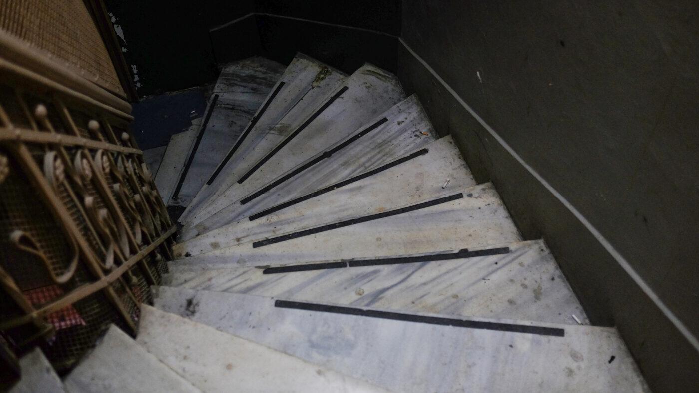 ofisin bulunduğu handaki merdivenleri göseren bir fotoğraf. Aşağıya doğru inerken solda trabzan var, sağda yeşil renkli duvar. merdivenler mermerden ve dönerek iniyor.