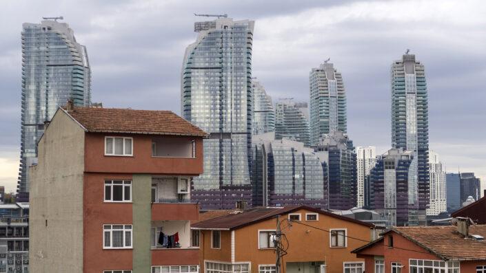Turuncu renkli eski apartmanların arkasından gökdelen rezidansların yükseldiği bir manzara..