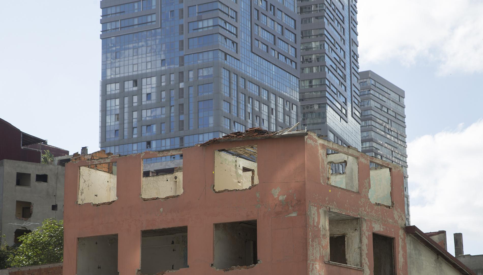 Yarı yıkılmış eski bir binanın ardında yükselen gökdelenimsi rezidans